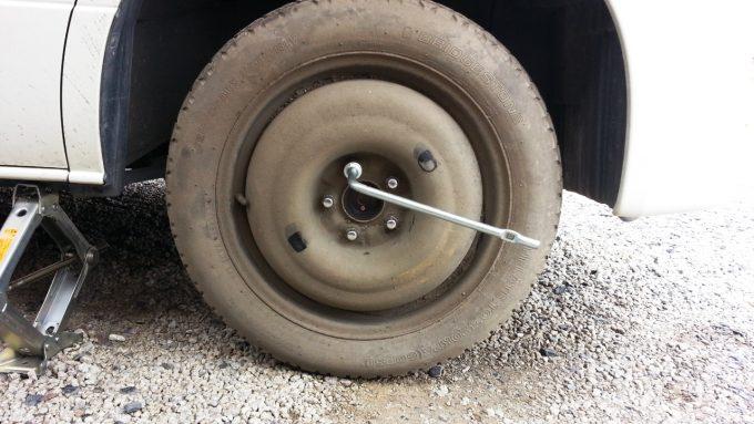 スペアタイヤのホイールナットを締め付けていく