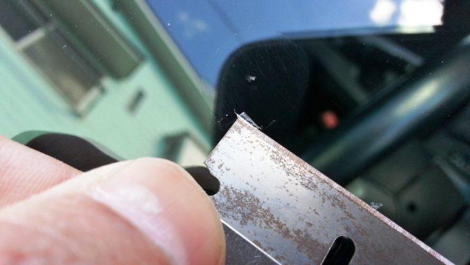 フロントガラスのDIYリペアキット付属のカミソリでレジンを取り除く