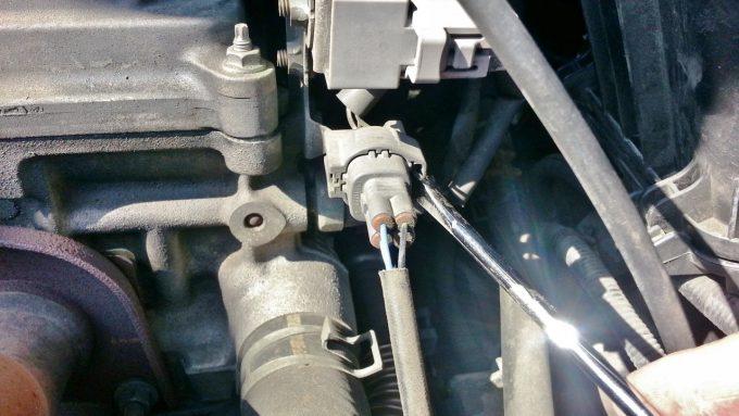 O2センサーのカプラーの間にマイナスドライバーを差し込む