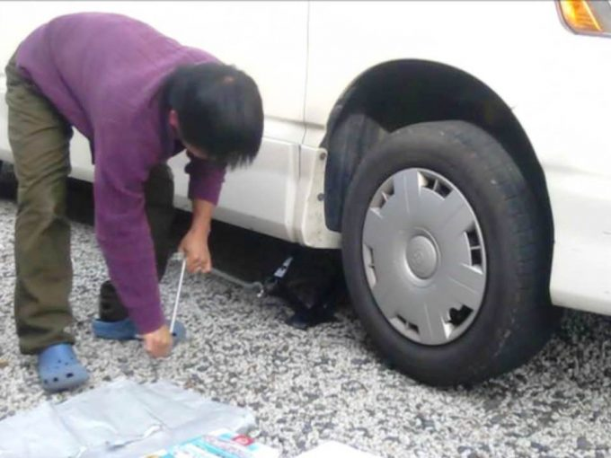 オイルを下から抜き取るためにジャッキを使って車を持ち上げる