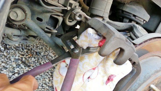 プライヤーと布切れを使ってブレーキのピストンを押し戻す