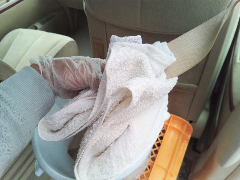 古タオルでシートベルトの水気を取る