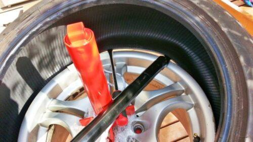 タイヤジェンジャーの長い棒を使ってタイヤを外している