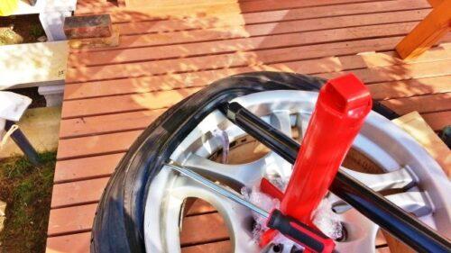 赤いタイヤチェンジャーの棒を軸にして、グル~っとレバーを回していけば、タイヤを取り外すことができる