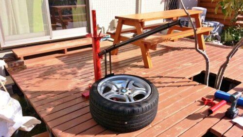 タイヤチェンジャーに付属のレバーを差し込み、下側にグイッと力を入れます。